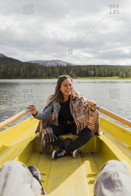 Finland- Lapland- laughing woman wearing a blanket in a rowing boat on a lake