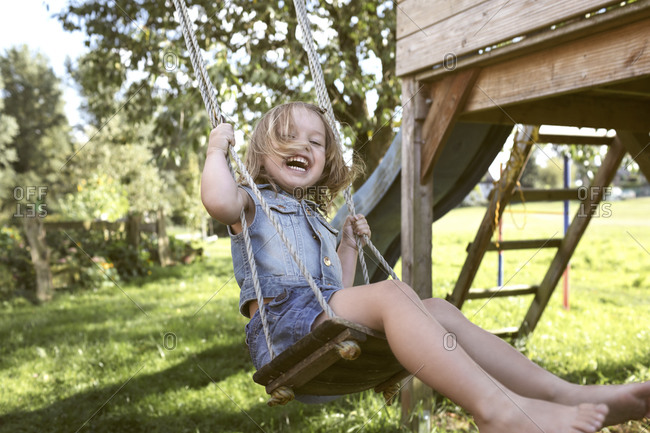 Laughing little girl sitting on swing in the garden