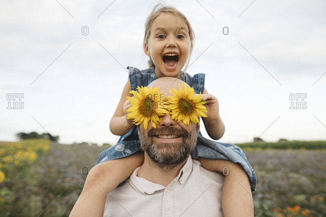 Sunflowers covering eyes of playful man with daughter in a field