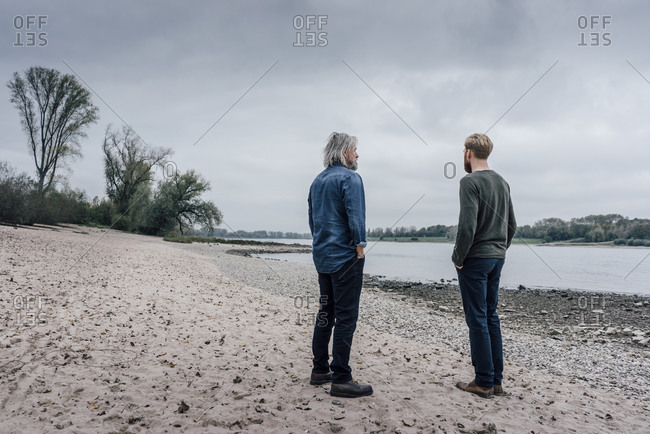 Father and son taking a stroll at Rhine river- meeting to talk
