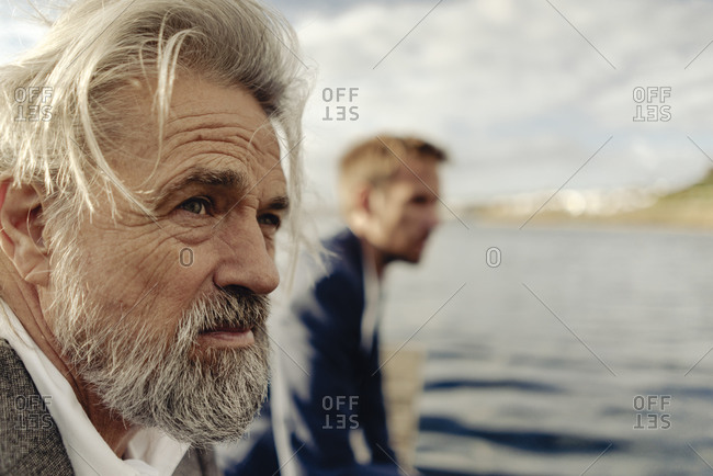 Portrait of serious senior man at a lake with man in background