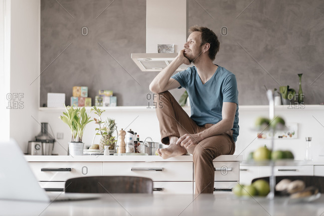 Smiling man sitting on kitchen counter looking at distance