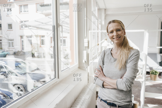 Portrait of smiling woman standing at the window
