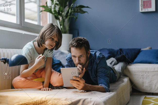 Father and son watching a movie on tablet at home