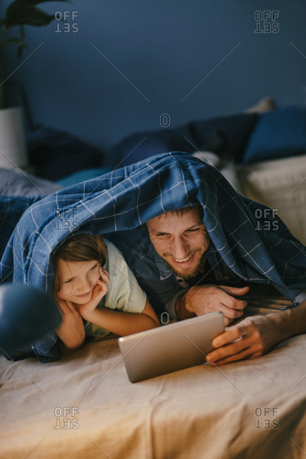 Happy father and son watching a movie on tablet under blanket