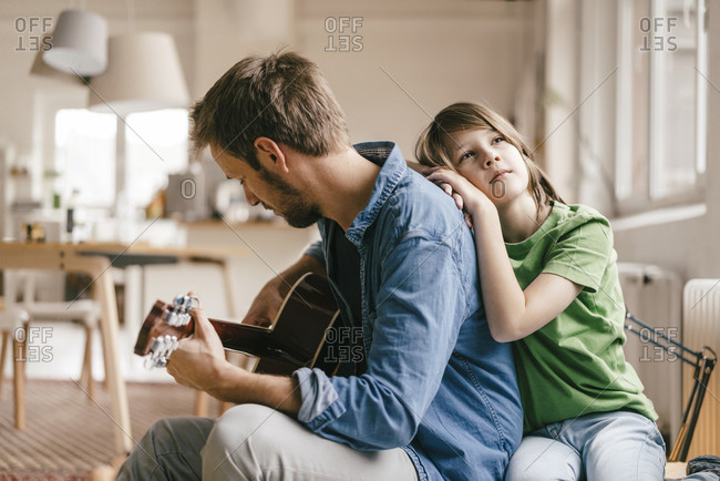 Son leaning against father playing guitar at home