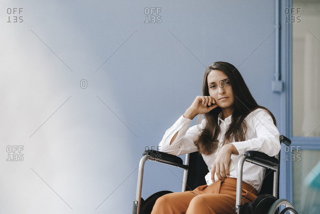 Young handicapped woman sitting in wheelchair- looking worried