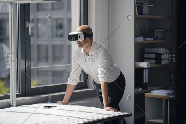 Businessman standing in his office- using VR glasses