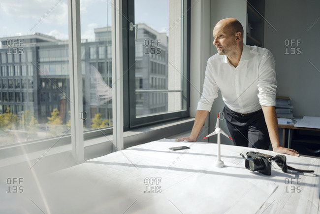 Engineer working in his office with model of a wing's wheel on his desk