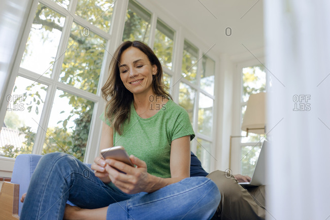 Smiling mature woman sitting on couch at home using cell phone with man in background