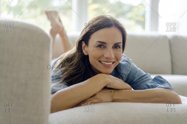 Portrait of smiling mature woman lying on couch at home