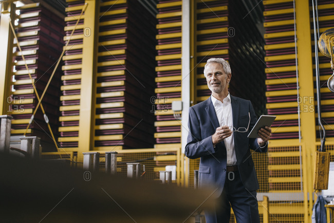 Successful entrepreneur standing in his company- using digital tablet