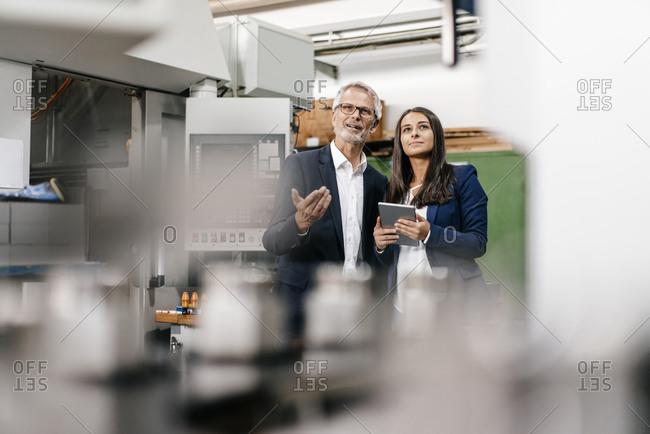 Businessman an woman in high tech enterprise- having a meeting in factory workshop