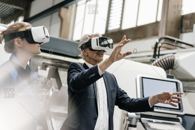 Businessman and skilled worker in high tech enterprise- using VR glasses