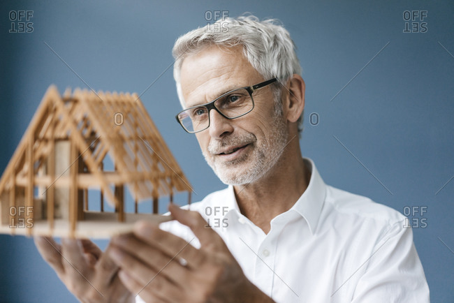 Successful architect looking at model of a house