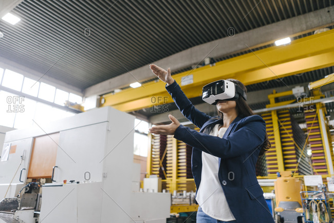 Young woman working in distribution warehouse- wearing VR glasses