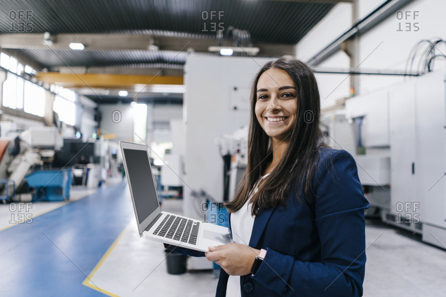 Confident woman working in high tech enterprise- holding laptop