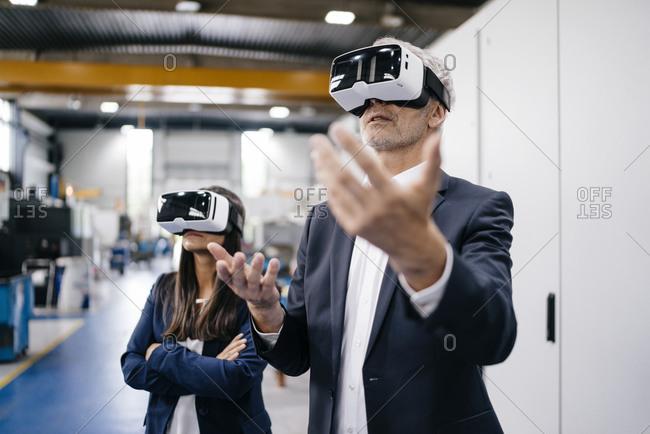 Businessman an woman in high tech enterprise- using VR glasses