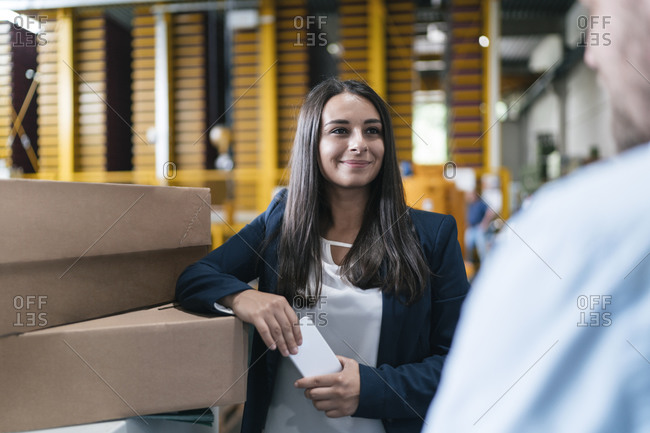 Young woman working in distribution warehouse- talking to colleague