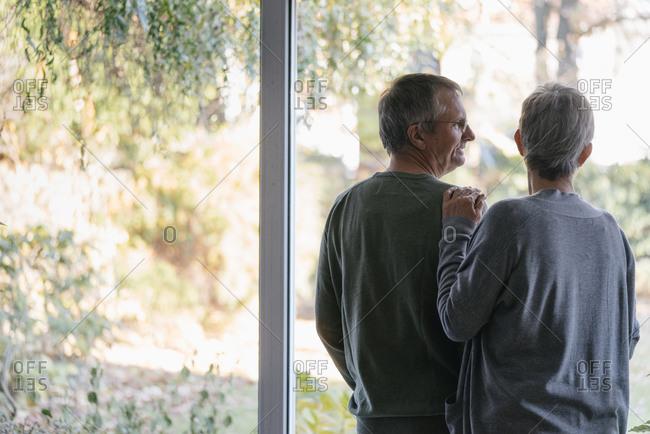 Senior couple standing at panorama window