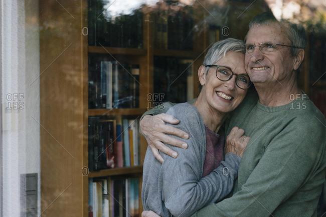 Portrait of happy senior couple hugging behind windowpane