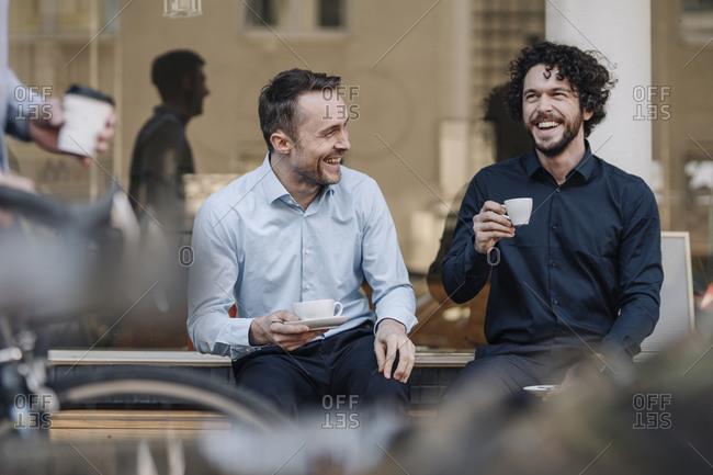 Friends sitting in front of coffee shop- talking- drinking coffee