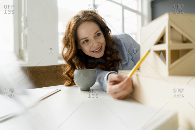 Portrait of smiling redheaded woman looking at architectural model