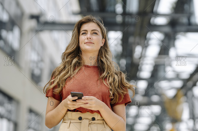 Portrait of smiling young brunette woman using smartphone- looking at distance