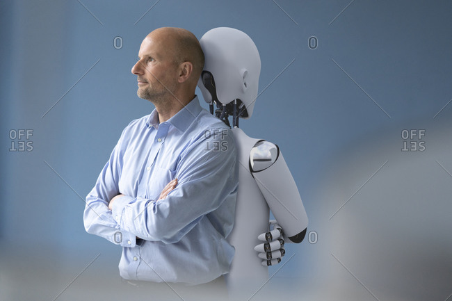Businessman standing back to back with robot