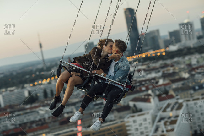 Young couple in love- riding chairoplane on a fairground
