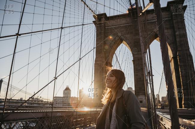 USA- New York- New York City- female tourist on Brooklyn Bridge at sunrise