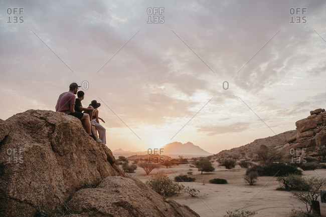 Namibia- Spitzkoppe- friends sitting on a rock watching the sunset