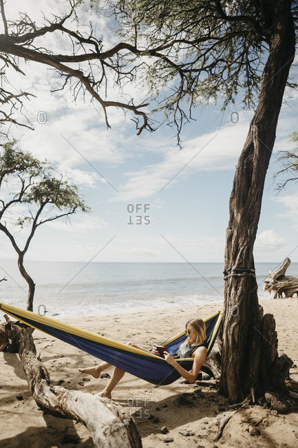 Young woman reading book while resting in hammock at beach- Maui- Hawaii- USA