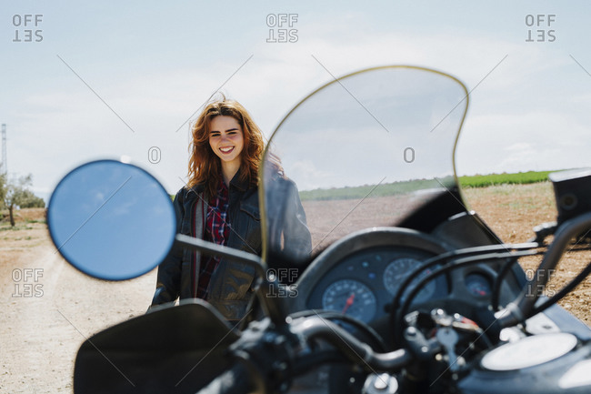 Portrait of happy redheaded woman with motorbike on dirt track
