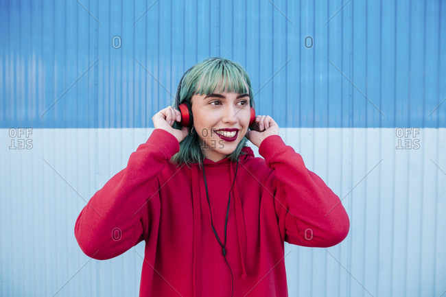 Portrait of smiling young woman with blue dyed hair listening music with headphones