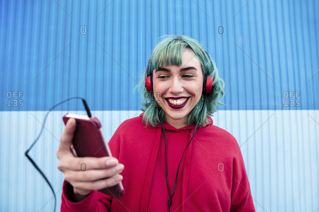 Portrait of laughing young woman with blue dyed hair with headphones taking selfie with smartphone