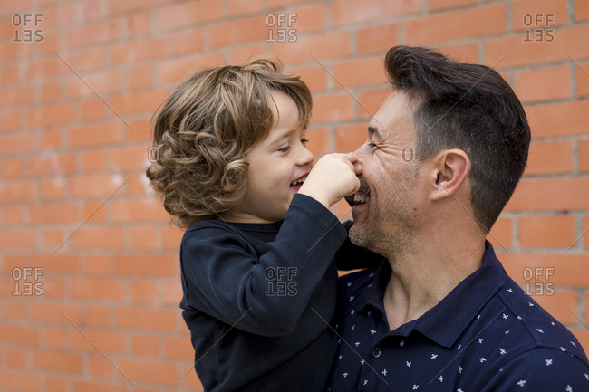 Playful father and son at brick wall