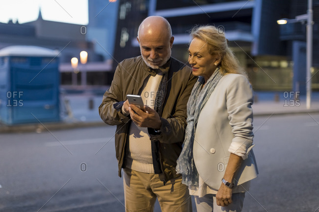 Spain- Barcelona- senior couple sharing cell phone in the city at dusk