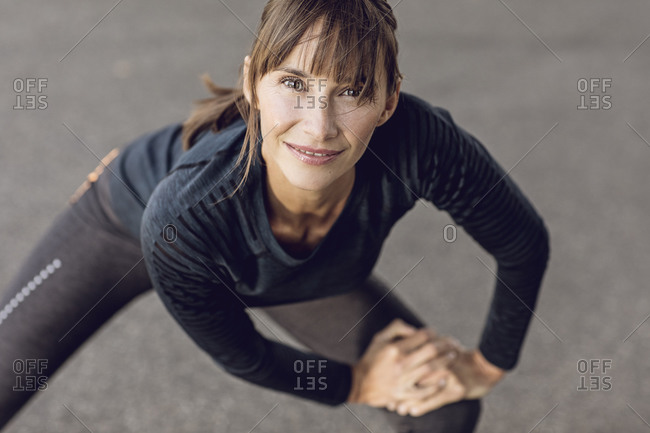 Sportive woman doing her fitness training outdoors- stretching