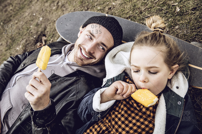 Father and daughter resting on skateboard- eating ice cream
