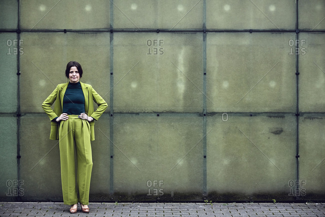 Portrait of confident businesswoman wearing green suit standing at a wall