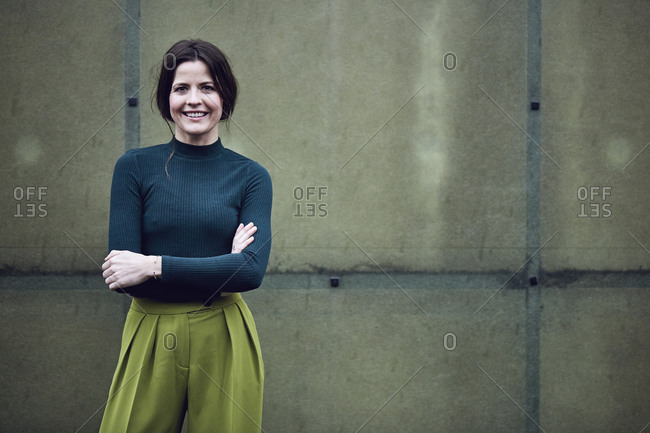 Portrait of smiling businesswoman standing at a green wall