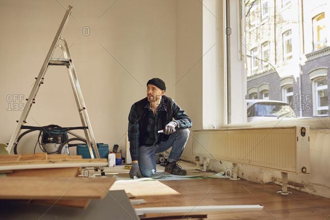 Man refurbishing shop location- laying flooring