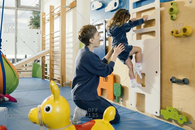 Pre-school teacher helping little girl climbing up a wall