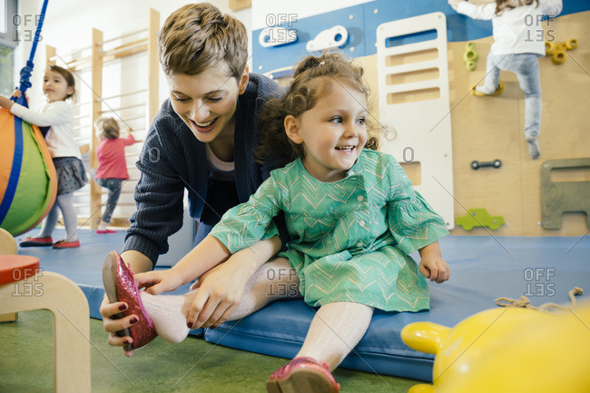 Pre-school teacher helping little girl putting a shoe on