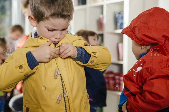 Boy putting on his raincoat in kindergarten
