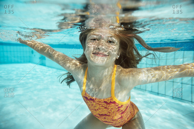 Portrait of smiling girl under water in swimming pool