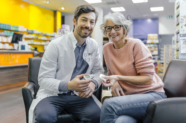Portrait of smiling pharmacist and customer with blood sugar meter in pharmacy