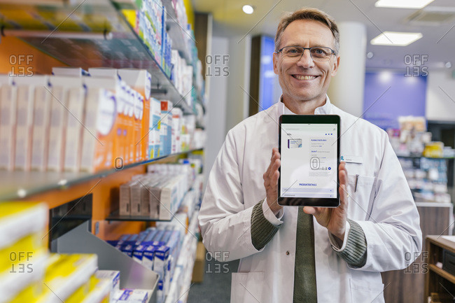 Portrait of smiling pharmacist in pharmacy holding tablet with digital order