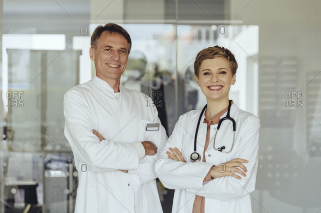 Two confident doctors standing in practice- with arms crossed